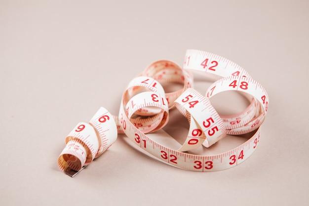 白い表面に白い測定テープ