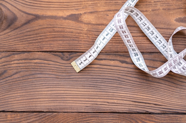 White measuring tape of a tailor lies in corner on dark wooden background. copy space for text