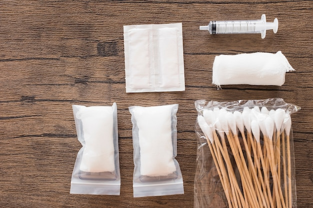 White medical cotton gauze bandage; syringe and pack of cotton swab on wooden table
