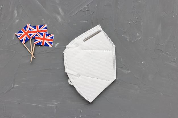 Белая медицинская маска для лица и флаги великобритании, концепция covid