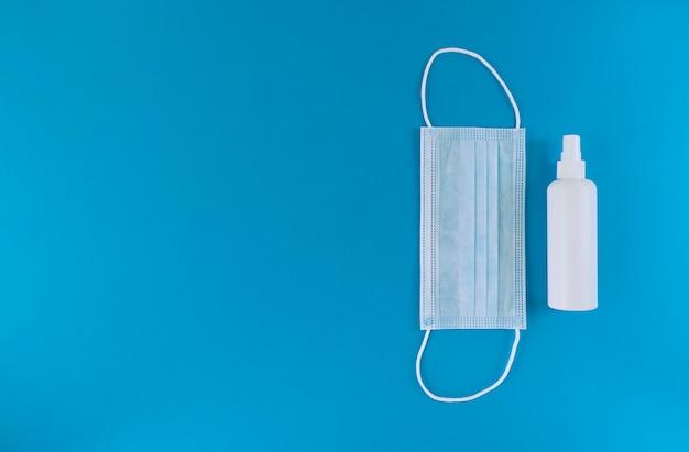 Белая медицинская маска и дезинфицирующее средство для рук во флаконе с распылительным колпачком справа от синей поверхности. простая плоская планировка с копией пространства. медицинская концепция.
