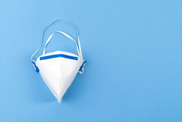 White medical mask on blue background.