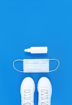 파란색 배경에 흰색 의료 마스크, 트레이너 및 손 소독제. 단색 수직 평면 배치.
