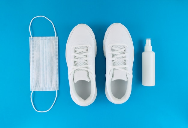 White medical mask, trainers, and hand sanitizer on a blue background. monochrome flat lay. quarantine outfit.