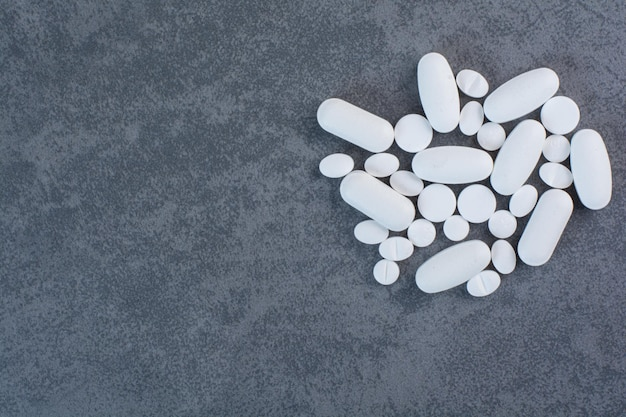 White medical pills on marble surface