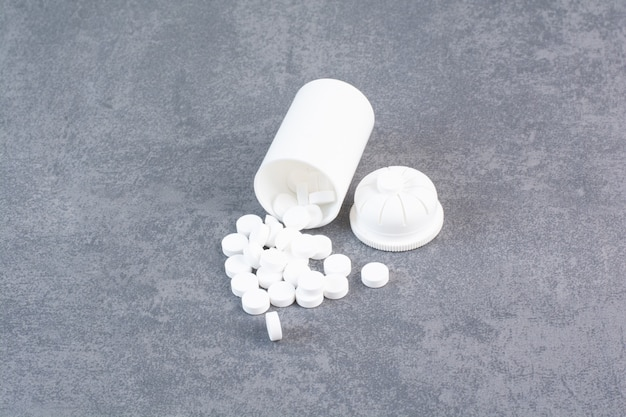 White medical pills out of plastic container.