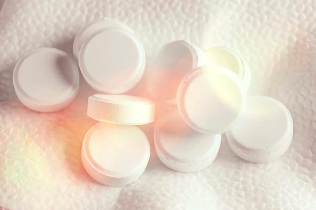 白い薬の丸薬は、ボケ味のライトと白い背景の上にあります。医療および製薬のトピックに関する背景画像。医学、薬局、ヘルスケア。痛みのない生活。
