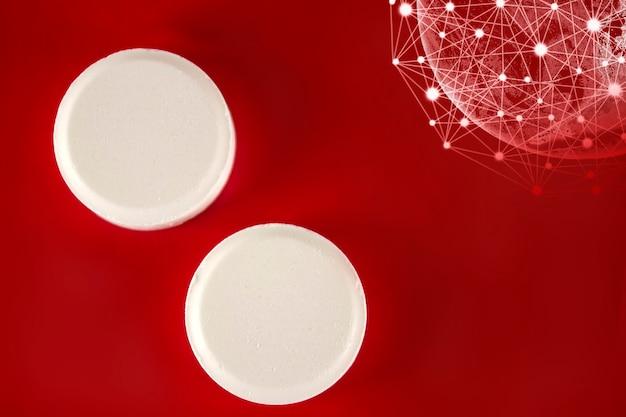 白い薬の丸薬は、赤い背景の上の仮想ホログラム地球と一緒に横たわっています。医学、薬局、ヘルスケア。テキスト用の空のスペース。