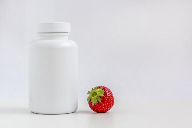 알약 또는 비타민식이 보충제 및 딸기 용 흰색 약 병.