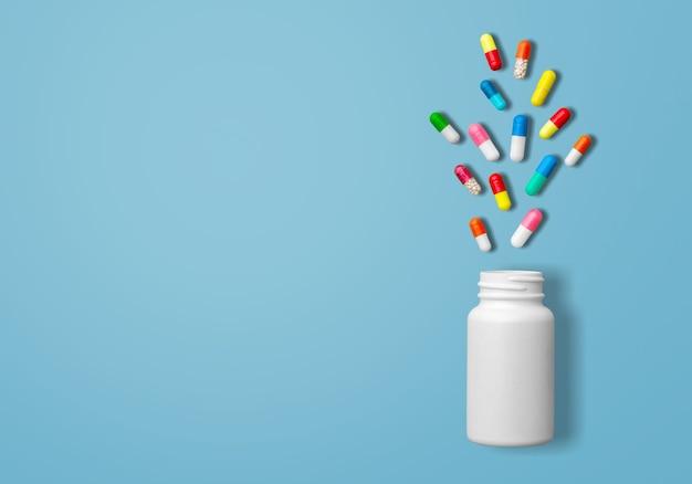 白い薬瓶、黄色い錠剤、灰色の錠剤、白い錠剤、青い背景の赤い錠剤、