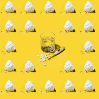 Белый медицинский респиратор kn95 маска бесшовные модели на ярко-твердом желтом со стаканом воды, медицинским термометром и таблетками в центре.