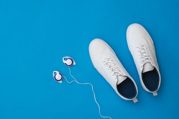 Белые мужские кроссовки и наушники-вкладыши на синем фоне. спортивный стиль. вид сверху.