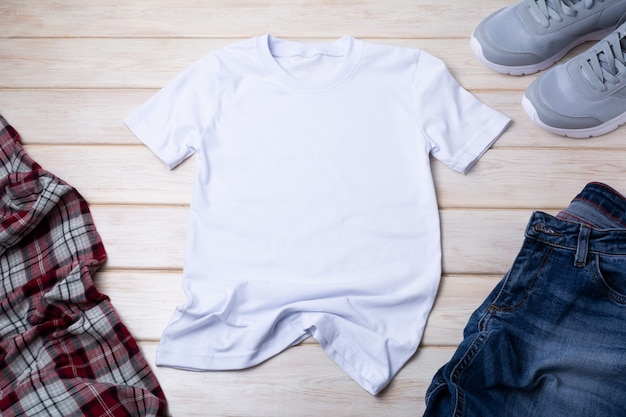 White mens cotton t-shirt mockup with dark denim jeans, gray running shoes and checkered shirt. design t shirt template, tee print presentation mock up