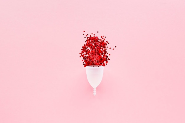 White menstrual cup with red hearts symbolizing menstruation on pink