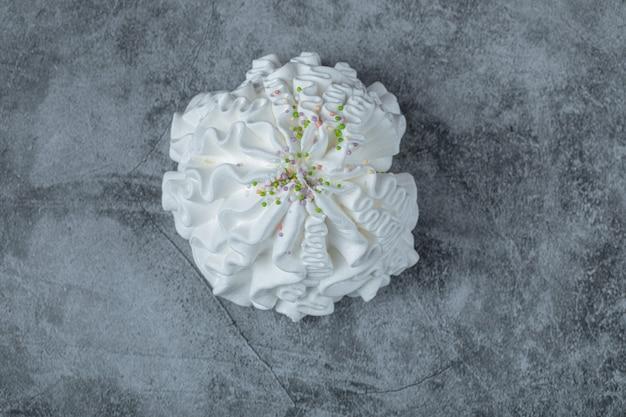 コンクリートのテーブルの上の白いメレンゲクッキー。