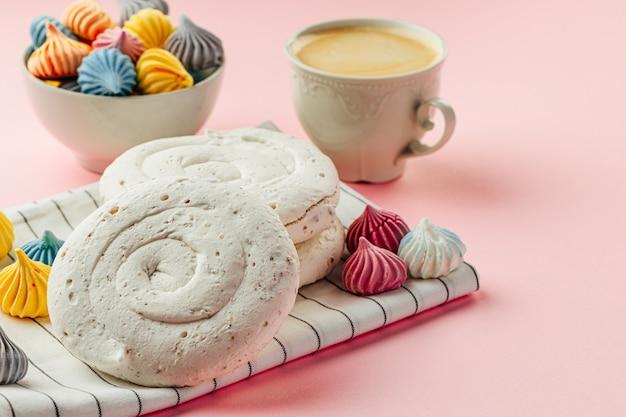 Белое безе печенье на розовом фоне с красочными мини-безе