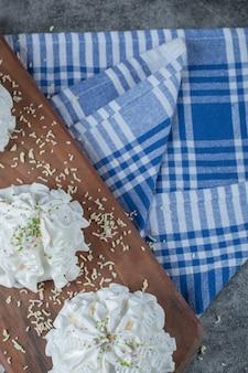 青いタオルの上の木の板にココナッツパウダーと白いメレンゲクッキー。