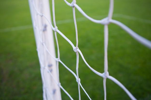 サッカー場、サッカーゴールの白いメッシュのクローズアップ。グリーンフィールド。