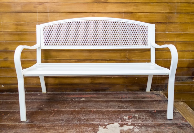 White metal bench near the wooden terrace.