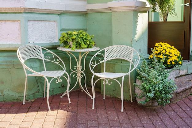 야외에 있는 흰색 금속 의자와 테이블은 휴식과 휴식을 제공합니다.