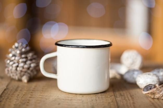 ホワイトメタルのコーヒーカップ、古い木製のテーブルのマグカップ