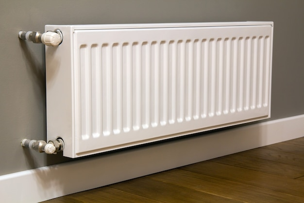 White metal heating radiator mounted on gray wall inside a room.