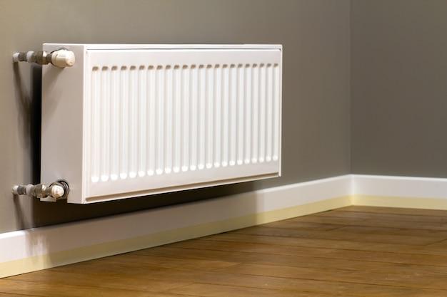 Радиатор отопления белый металл установлен на серой стене внутри комнаты.