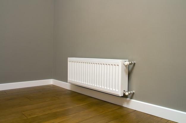 방 안의 회색 벽에 흰색 금속 난방 라디에이터가 장착되어 있습니다.