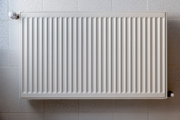 White metal heating radiator mounted on a wall in room interior.