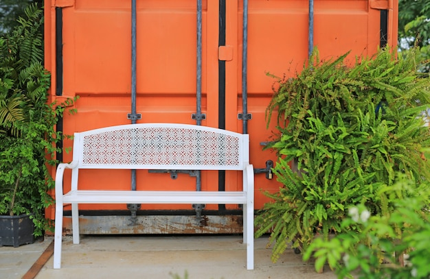 White metal long chairs in the garden against orange container.