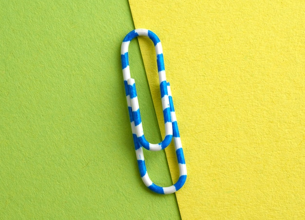 White metal paper clip on a green background