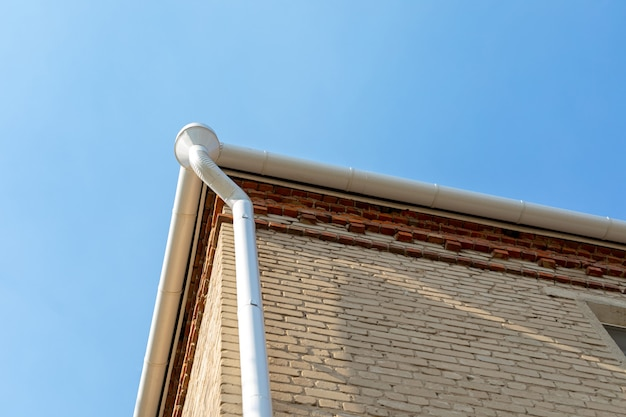 Белая металлическая труба от водостока на стене кирпичного дома. держатель водосточной системы на крыше. водосток на крыше дома. кровельный дренаж. отвод воды с крыши.