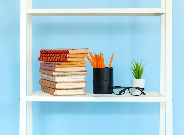 White metal rack with books against blue surface