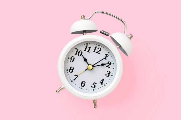 ピンクの背景、上面図に丸い文字盤とホワイトメタルのレトロな目覚まし時計。ミニマルなデザイン。