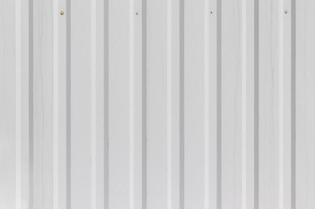 垂直の波形の縞模様の白い金属の壁またはフェンス