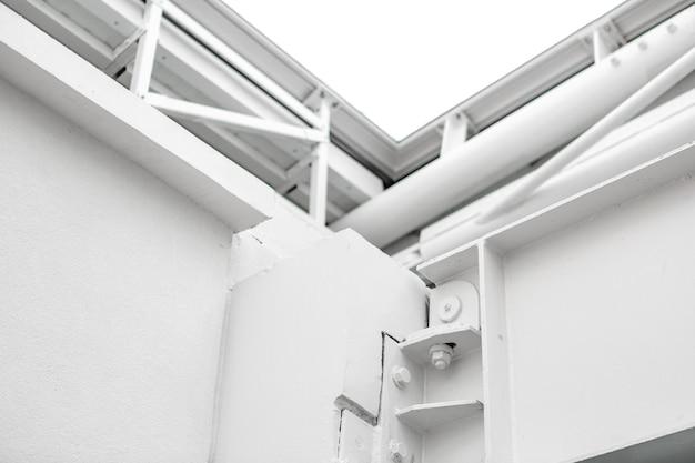 Белое металлическое здание и трубы