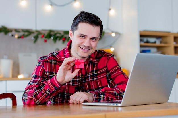 Белый мужчина среднего возраста в красной футболке держит подарочную коробку и ищет продажи в интернете через портативный компьютер во время рождества.