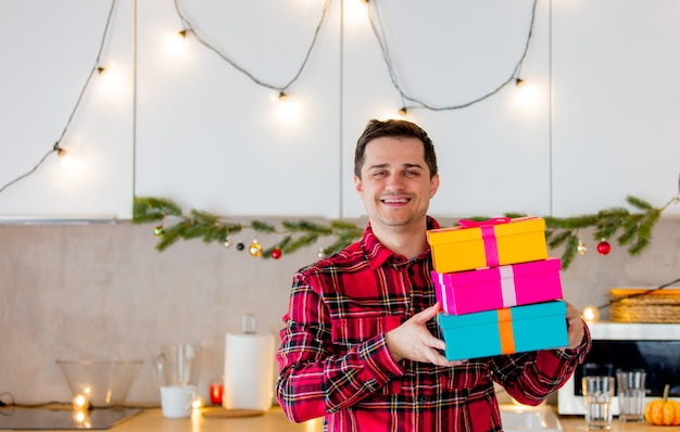 White middle age man in red shirt holding a gift boxes in kitchen in christmas time.