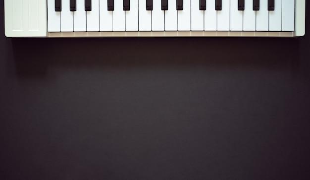 Белая миди-клавиатура на темном фоне, плоская планировка, вид сверху
