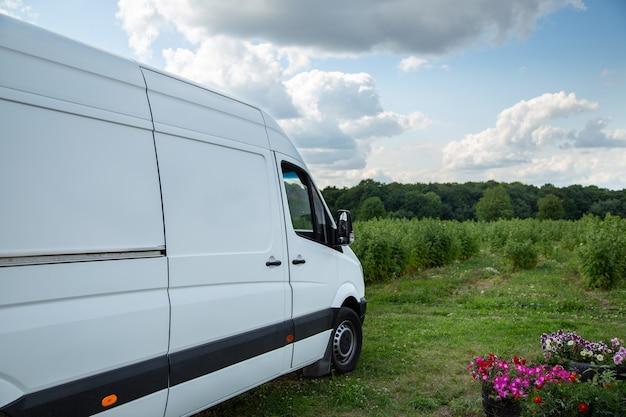 Белый мини-грузовик привез товар. доставка груза. транспорт.