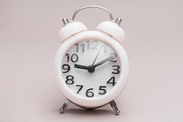 Белый миниатюрный будильник на цветном фоне