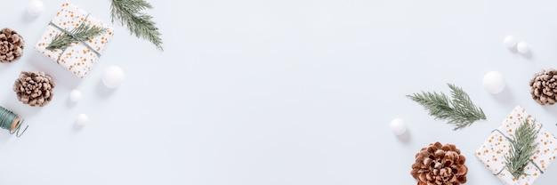 크리스마스 트리 분기, 장식 및 원뿔, 평평한 위치, 복사 공간, 웹 배너가 있는 흰색 최소 크리스마스 테두리
