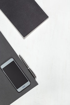 White minimal office desk table with smartphone, pen and closed black cover notebook. top view with copy space. flat lay.