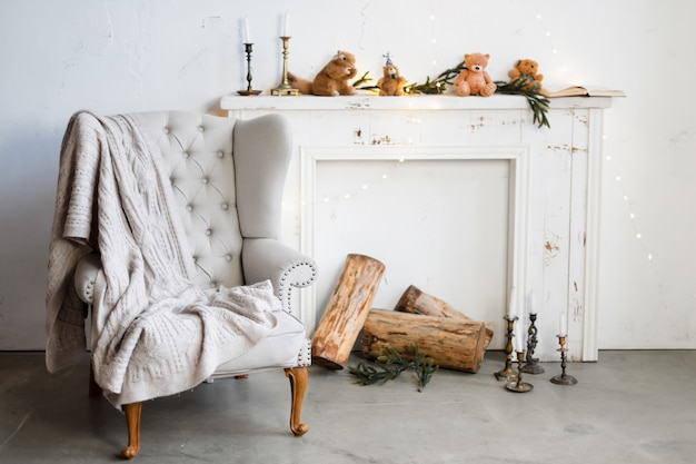 White minimalist loft interior with fireplace, armchair and christmas decorations.