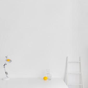 Белое минималистичное рабочее пространство с лестницей и лимоном