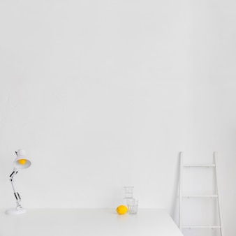 White minimalistic workspace with ladder and lemon