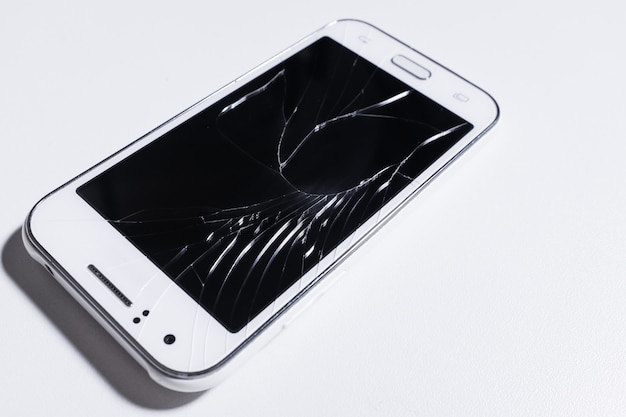 A white mobile phone is broken screen on white.blank for copy space.
