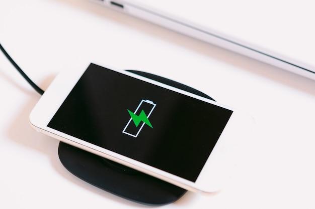 화면에 녹색 번개가 있는 배터리 로고가 있는 흰색 모바일 스마트 폰, 흰색 작업 테이블에 있는 노트북 옆에 케이블이 없는 충전기 베이스에서 충전