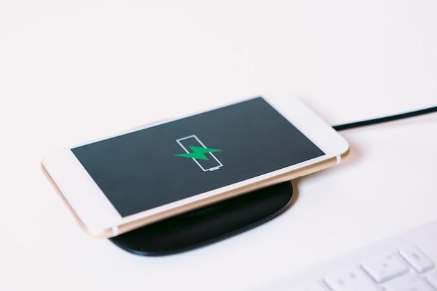 화면에 녹색 번개가 있는 배터리 로고가 있는 흰색 모바일 스마트 폰, 흰색 작업 테이블에 케이블이 없는 충전기 베이스에서 충전