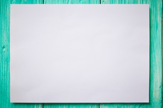 White mockup blank paper on green wooden background.